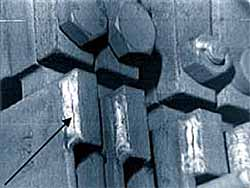 Fig.7. Cracked burst can detector hanger welds. Arrow shows location of crack.