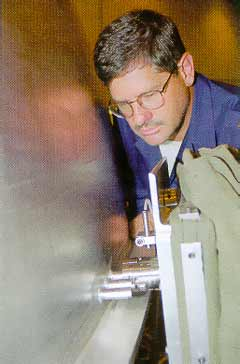 b) The friction plug welding apparatus in action.