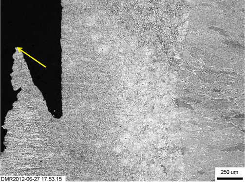 Figure 16. Initiation region (shown by arrow) of fractured W01 specimen from just behind the fatigue precrack tip
