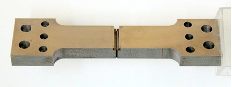 Figure 5 SENT specimen design with bolt holes (a) which can be gripped inside a thermal chamber