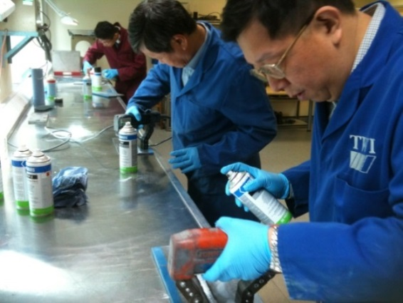 SOIC delegates experiment with dye penetrant testing.