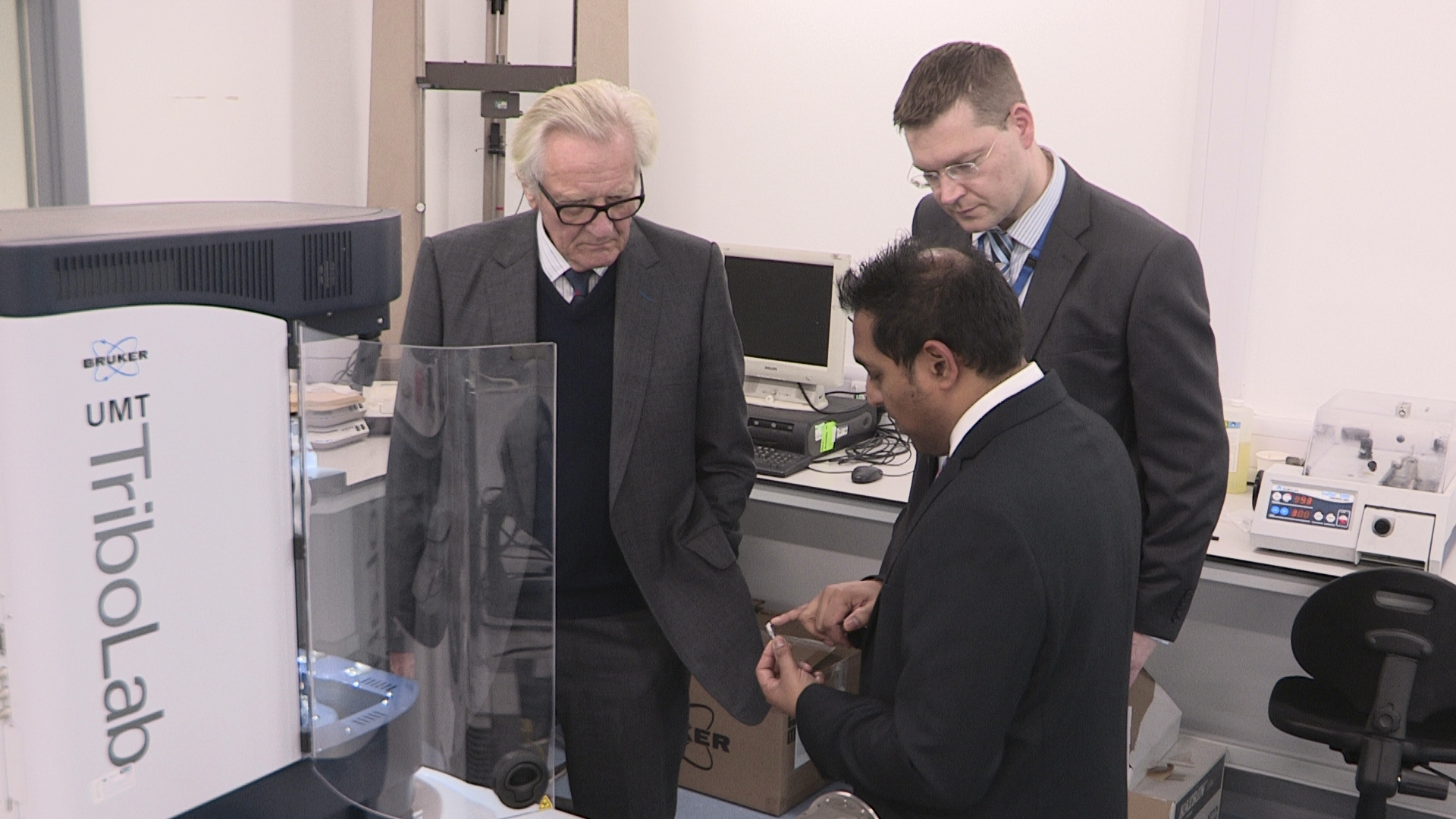 TWI's Amit Rana demonstrates the effects and measurement of frictional force on surfaces in constant contact with Lord Heseltine and TWI Operations Director Mike Russell