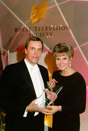 Journalist John Dadson accepts first prize from TV presenter Angela Rippon