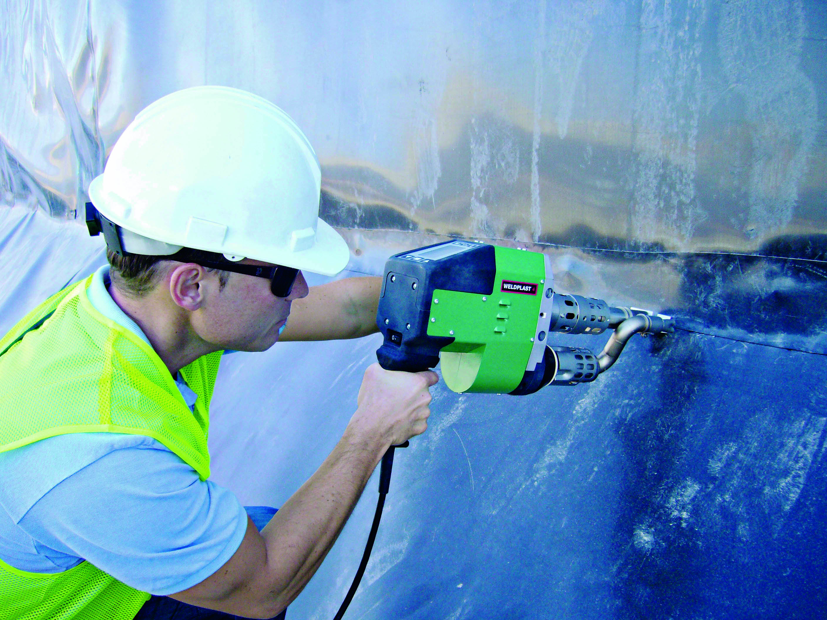 An engineer uses plastic welding equipment to join a geomembrane lining