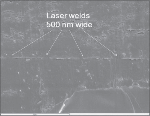 Fig. 6 Laser welded sample in cross section. The tops of the 5 μm wide tracks have been welded to the top sheet of PMMA. Gaps with a height of a few hundred nanometres have been left on either side of the welded tracks. (scale bar 6 μm).